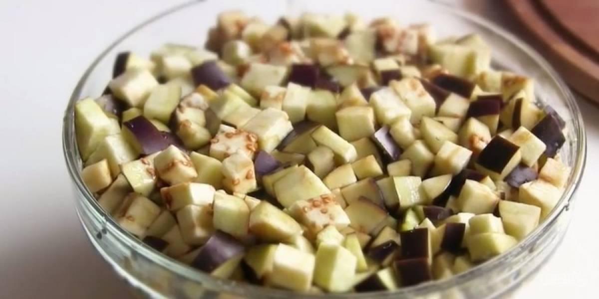 1. Нарежьте баклажаны кубиками, посолите, перемешайте и оставьте на несколько минут. Лук и помидоры нарежьте кубиками. На разогретом растительном масле обжарьте нарезанный лук до прозрачности.