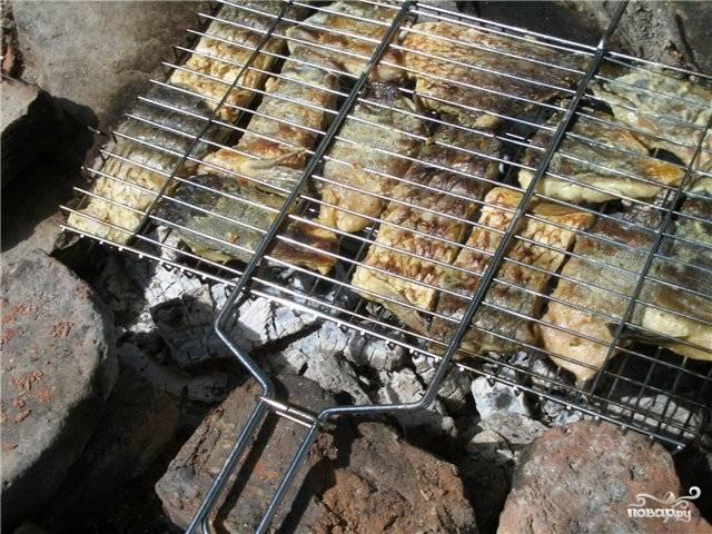 Через 2-3 часа достаем кастрюлю, нанизываем куски рыбы на шампуры или укладываем на решетку, и запекаем на углях. Если карп был пойман не в супермаркете, а в естественных условиях — пропекайте как следует, чтобы не осталось крови, т.е. до образования румяной хрустящей корочки. В процессе приготовления можно сбрызгивать мясо чистой водой с небольшим добавлением лимонного сока и соевого соуса.