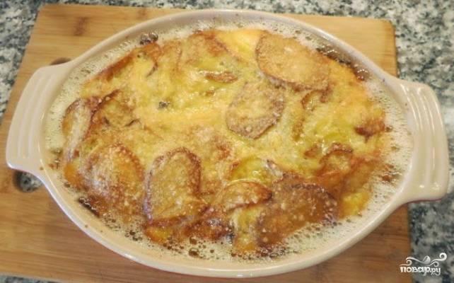 Форму для запекания смажьте растительным маслом и выложите на дно картофель, чередуя его слоями с луком. Для заливки разбейте яйца и перемешайте их с солью, перецем и натёртым на крупную или мелкую тёрку сыром. Этим соусом равномерно залейте овощи.