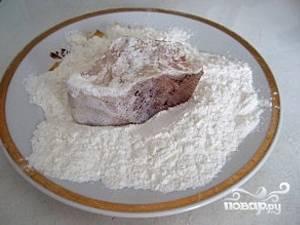 После того, как рыбка замариновалась, в плоскую тарелку насыпаем около 150 грамм муки. На плиту ставим сковородку, наливаем в нее масло и хорошенько обмакивая кусочки рыбы, отправляем их жариться.