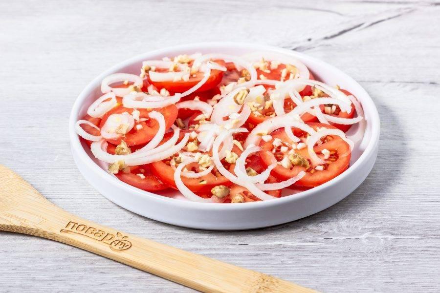 Затем посыпьте мелко рубленным чесноком и кусочками грецких орехов.
