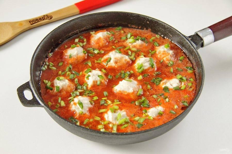 Добавьте по желанию любую свежую зелень, накройте сковороду крышкой и тушите клецки в соусе около 15 минут.