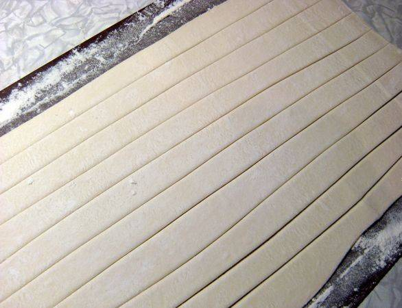 Размораживаем готовое слоеное тесто и раскатываем в пласт, толщиной примерно 0,4-05 см. Нарезаем раскатанное тесто на длинные полоски, шириной 1,5 см.