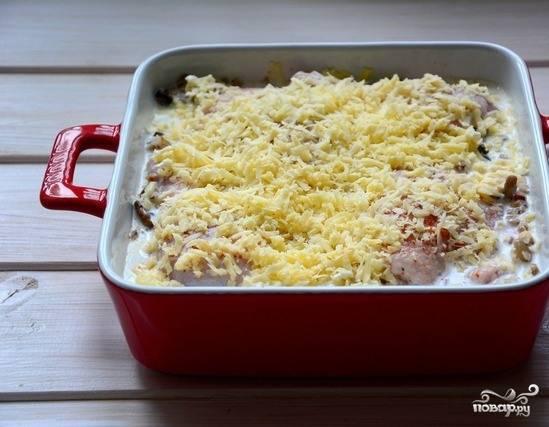 Откройте пакет со сливками, вылейте их поверх курицы с гречкой. Натрите любой твердый сыр и присыпьте им равномерно все блюдо. Выпекайте его в духовке, при температуре в 200 градусов около сорока минут.