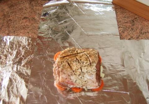 Куски фольги положить крест накрест. В центр положить порезанную морковь и чеснок, на него выложить мясо.