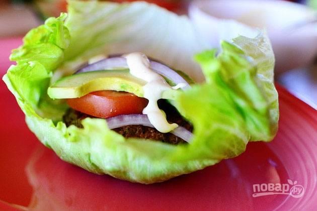 10.Выложите в салатный лист котлету, затем помидоры, авокадо и лук, полейте небольшим количеством майонеза.