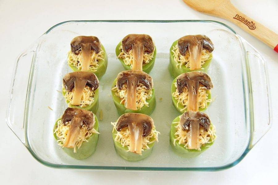 Сверху посыпьте тертым сыром. На сыр выложите пластины грибов и смажьте их маслом. Отправьте форму в духовку, разогретую до 180 градусов примерно на 15 минут.