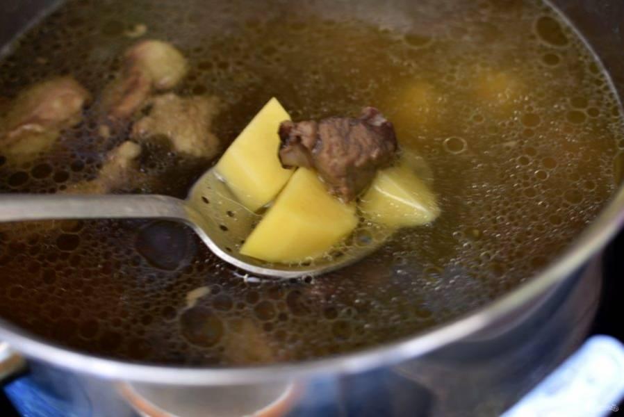 Сварите два литра крепкого бульона, процедите его, мясо нарежьте кусочками.  Опустите в суп картофель и варите почти до готовности. Верните в суп мясо.