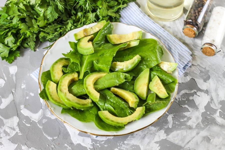 Авокадо разрежьте пополам и прокрутите две половинки плода в разные стороны, отделяя их друг от друга. Счистите кожуру и нарежьте ломтиками, выложите на листья шпината. Обязательно сбрызните нарезку лимонным соком, чтобы она не потемнела.