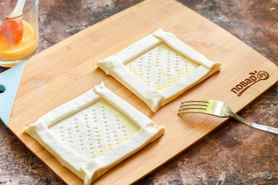 Из вырезанных полосок теста сделайте бортики для будущих слоек. Аккуратно придавите тесто друг к другу, края защипните. Центр заготовки проткните вилкой — как показано на фото.