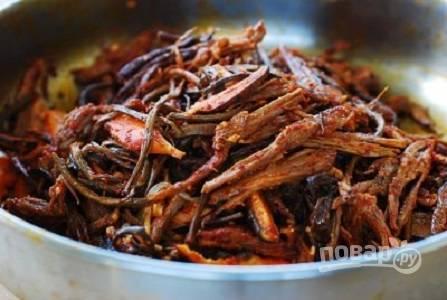 6. На сковороду выложите мясо, грибы и госари. Обжарьте несколько минут, аккуратно помешивая.