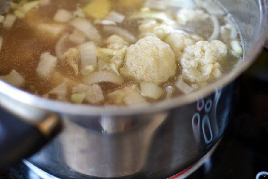 Опустите в кастрюлю лук и соцветия цветной капусты. Варите до мягкости.