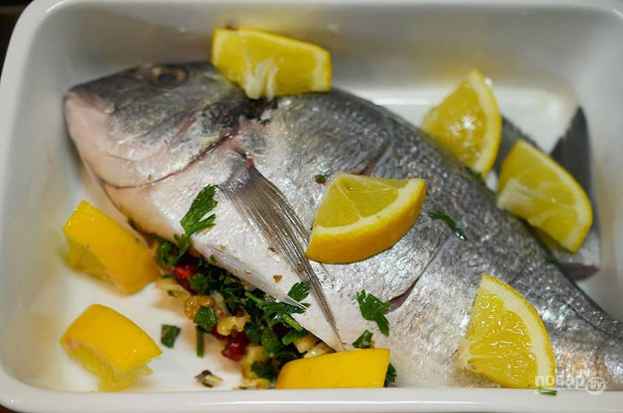 8. Выложите рыбу в форму, посолите. Полейте лимонным соком и обложите дольками лимона.