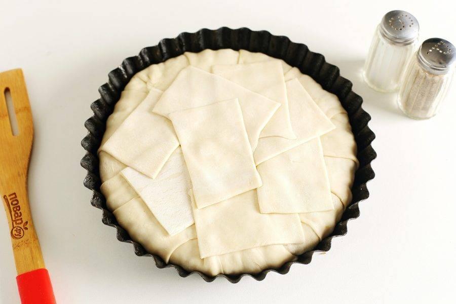 Затем закройте пирог сверху свисающими полосками теста. Посередине выложите тесто, чтобы не было просветов. Слегка прижмите тесто руками.