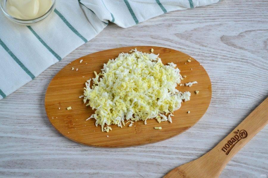 Яйца очистите и натрите на мелкой терке.