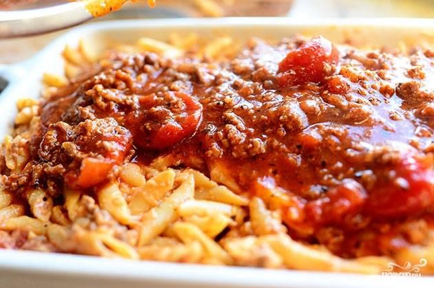 Выкладываем макаронную смесь в форму для запекания. Сверху заливаем оставшимся соусом, при желании - присыпаем небольшим количеством тертого сыра.