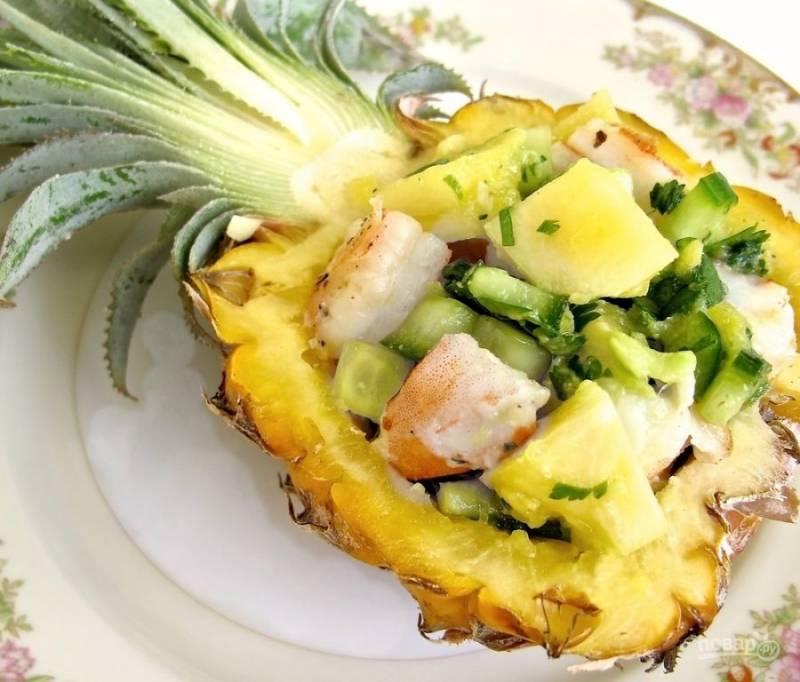 3.Креветки у меня уже отварные и очищенные, нарезаю их крупно и соединяю с остальными ингредиентами. Раскладываю салат по половинкам ананаса и подаю к столу.