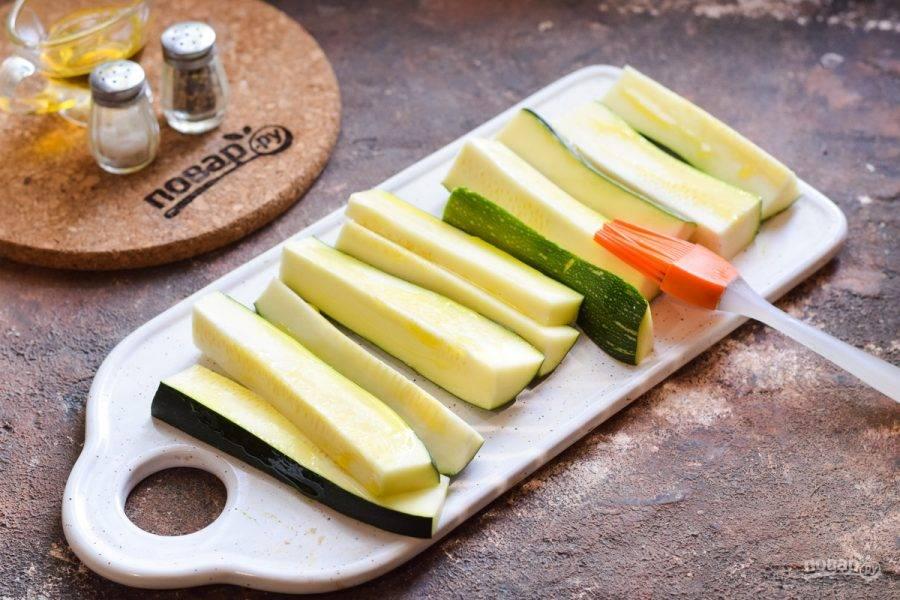 Цукини нарежьте дольками, смажьте каждую дольку растительным маслом.