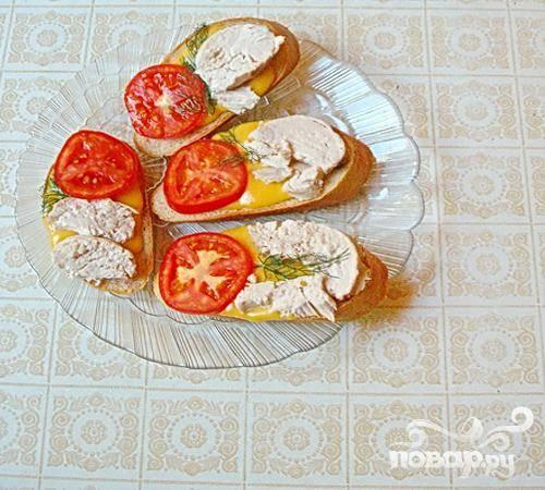 4.Порежем хлеб ломтиками, и теперь на каждый хлебный ломтик ложем нарезанный сыр, мясо ложем сверху на сыр, а ломтики помидоров – на мясные кусочки. Разогреем духовой шкаф, бутерброды выложим на противень, и минут десять подогреем их там. За это время все слои бутербродов слипнутся, они станут вкуснее, и есть их будет удобнее. Теперь бутерброды вынимаем и украшаем зеленью.