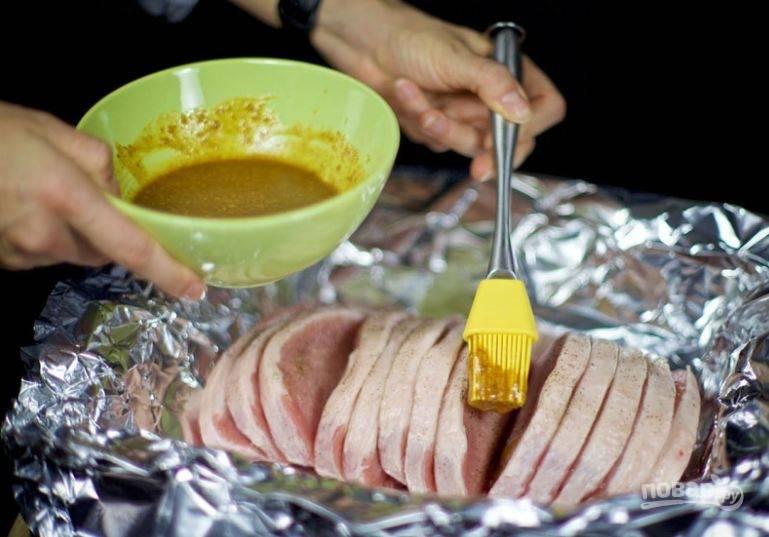 4. Кулинарной кисточкой смажьте маринадом все кусочки мяса, предварительно посыпав специями по вкусу. Накройте мясо фольгой и отправьте в холодильник на 10-12 часов.
