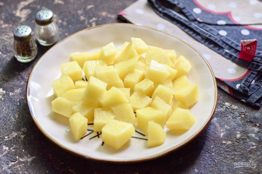 Картофель очистите, вымойте и просушите. Нарежьте картофель небольшими кубиками.