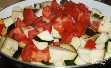 Баклажан, помидор и цукини нарезаем небольшими кубиками и добавляем на сковороду к луку с перцем. Солим, перемешиваем и накрываем крышкой. Тушим минут 15 на среднем огне.
