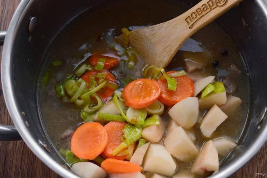 Картофель очистите, нарежьте кубиками одинаковыми по размеру с мясными. Добавьте картофель, морковь и лук-порей к мясу, готовьте в течение 20 минут.