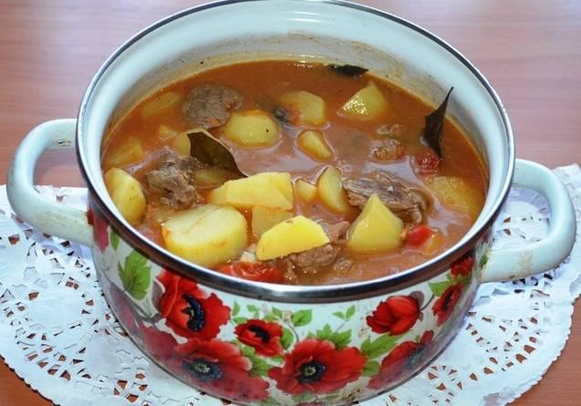Берем кастрюлю и выкладываем в нее часть картофеля, на него кладем часть обжаренного мяса с овощами, так чередуем картофель и мяса слоями. Затем наливаем в кастрюлю кипяченую воду или бульон так, чтобы жидкость почти полностью накрывала все ингредиенты, добавляем лавровый лист, солим и перчим блюдо по вкусу. Ставим кастрюлю на плиту и тушим все в течение часа (после закипания) на медленном огне.