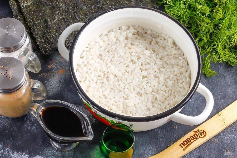 Рис промойте в воде, высыпьте в кастрюлю или казан с кипящей водой, добавьте туда же 2 щепотки соли и отварите на умеренном нагреве примерно 12-15 минут. Затем прогрейте рисовый уксус в микроволновке или в емкости, всыпьте в него сахар и перемешайте. Влейте уксус в рис и перемешайте, накройте крышкой и оставьте на 10 минут для пропаривания. Можно вместо крышки использовать марлевое полотно или тонкое полотенце.