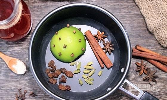 Чай залейте кипятком. Оставьте его на 15 минут. А пока в кастрюлю с толстым дном уложите яблоко, в которое воткните гвоздику, а также кардамон, бадьян, промытый изюм и корицу.
