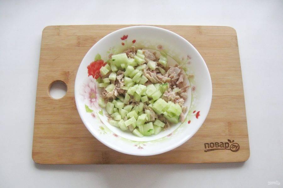 Огурец помойте, очистите и нарежьте кубиками. Выложите в салат.