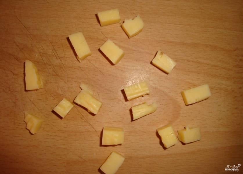 """Возьмите любой твердый сыр, который вы любите, нарежьте его на кубики небольшого размера. Отлично подойдут те сорта сыра, которые быстро и хорошо плавятся при высокой температуре (к примеру, """"Гауда"""")."""