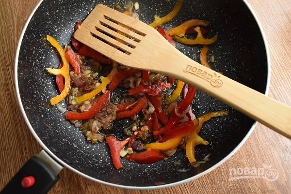 Масло разогрейте на сковороде, пассеруйте лук и чеснок до прозрачности. Посолите, поперчите по вкусу, добавьте сахар, дождитесь его растворения и готовьте до карамелизации лука. Выложите нарезанный перец, перемешайте и готовьте 1 минуту.