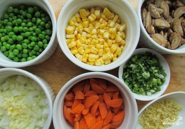 Подготовьте все ингредиенты. Нарежьте грибы, морковь, репчатый лук и чеснок. Сложите в чашку горошек. Отделите кукурузные зёрна от початка.