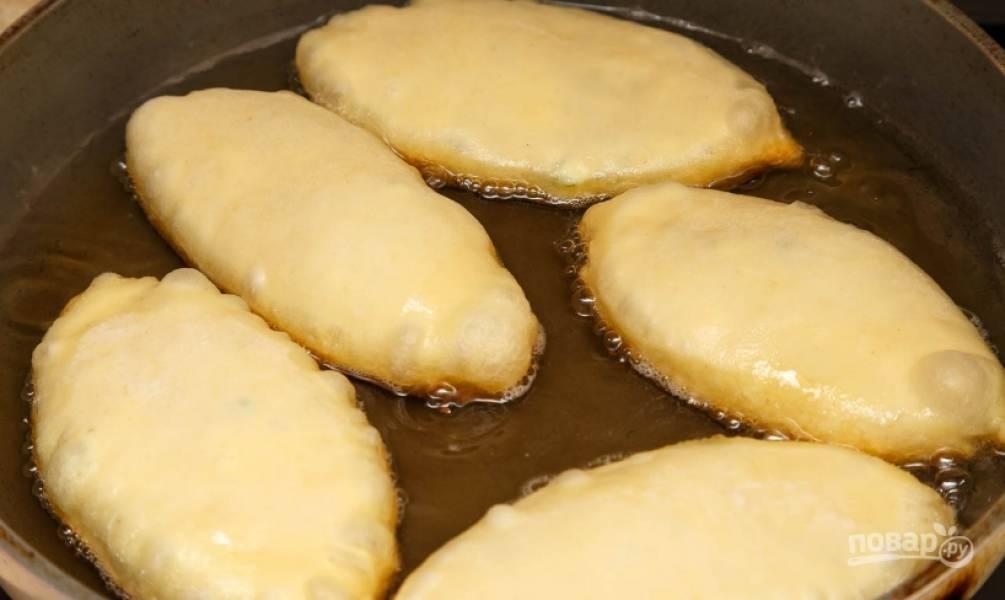 12. В сковороду наливаю подсолнечное масло, отправляю ее на огонь, на раскаленную поверхность выкладываю немного приплюснутые пирожки.