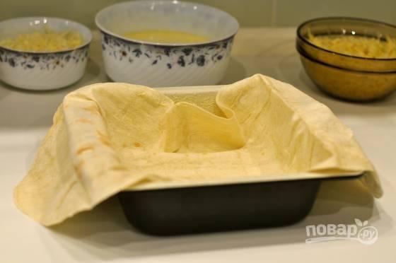 Прямоугольную глубокую форму для выпечки смажьте маслом. На дно выложите один лист лаваша так, чтобы края свисали на 10-15 см.