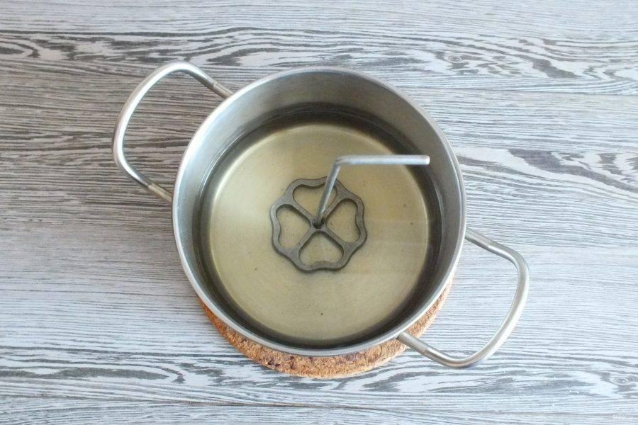 В кастрюле разогрейте растительное масло, после убавьте огонь до чуть ниже среднего. Масло не должно быть перекаленным. Опустите специальную форму в разогретое масло на 10-15 секунд. Она за это время хорошо прогреется.