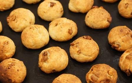 Отрываем от теста небольшие кусочки и лепим шарики, величиной чуть больше грецкого ореха. Выкладываем шарики из теста на противень и выпекаем минут 30 до румяного цвета. Температура выпечки 170-180 градусов. Проверить готовность печенья можно деревянной зубочисткой.