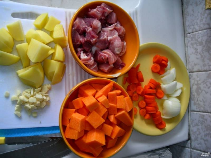 Подготовьте все ингредиенты. Мясо порежьте кубиками, тыкву — крупными кубиками. Лук, морковку, картошку режем крупно. Чеснок порубите мелко, но не слишком.