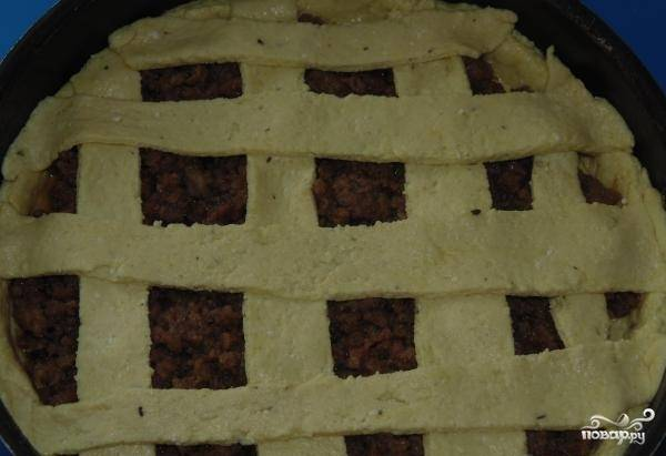 11.Из второй части теста вырезаем полоски для украшения пирога, выкладываем их поверх начинки, прикрепляя к бортика будущего пирога.