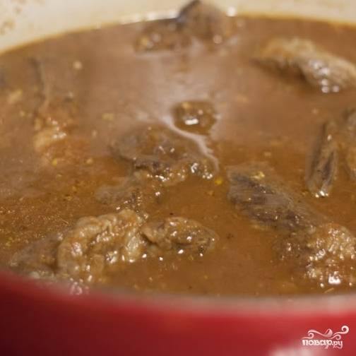 8. В утятницу выложите содержимое сковороды, добавьте куриный и говяжий бульон, лавровый лист, тмин и майоран, все перемешайте. Туда же сложите мясо, накройте крышкой и отправляйте в духовку.
