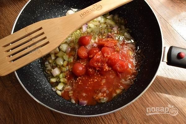 С консервированных помидоров снимите кожицу, добавьте их на сковороду, перемешайте, тушите в течение 5 минут.
