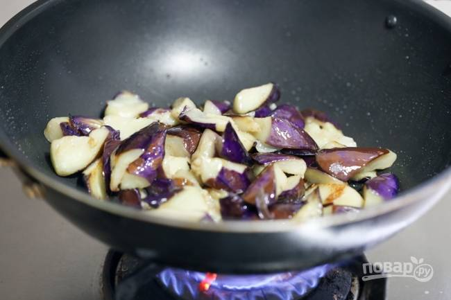 2. Разогрейте растительное масло и выложите баклажаны. На среднем огне обжарьте до румяности со всех сторон. Снимите и отложите пока в сторону.