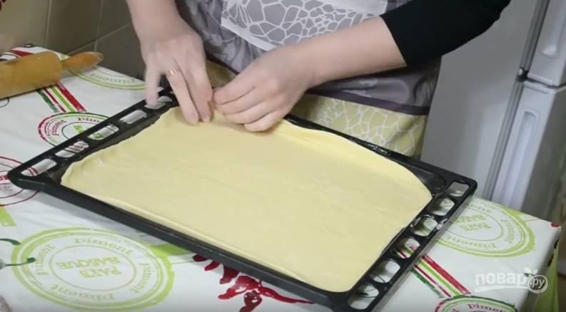 Разделите тесто на две части. Большую из ник тонко раскатайте. Припылите противень мукой и перенесите на него тесто. Сформируйте бортики.