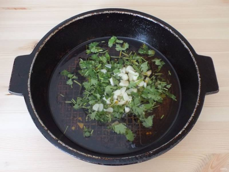 В масло, в котором жарились перцы, добавьте измельченный чеснок, нарезанную кинзу, соль, сахар. Поставьте на огонь и после закипания проварите 3-4 минуты.