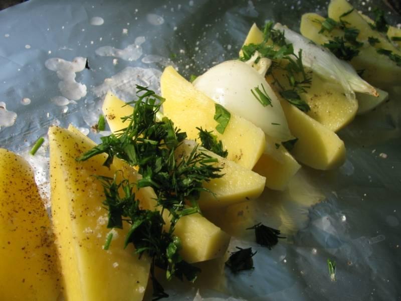 Далее мы расстилаем на ровной поверхности лист фольги, выкладываем на него несколько долек картофеля (8-10) и перья лука. Посыпаем все свежей зелень, молотым перцем и солью.