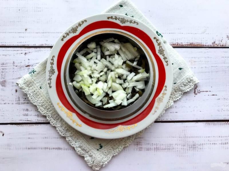 Лук очистите от шелухи, мелко нарежьте и выложите поверх морской капусты.