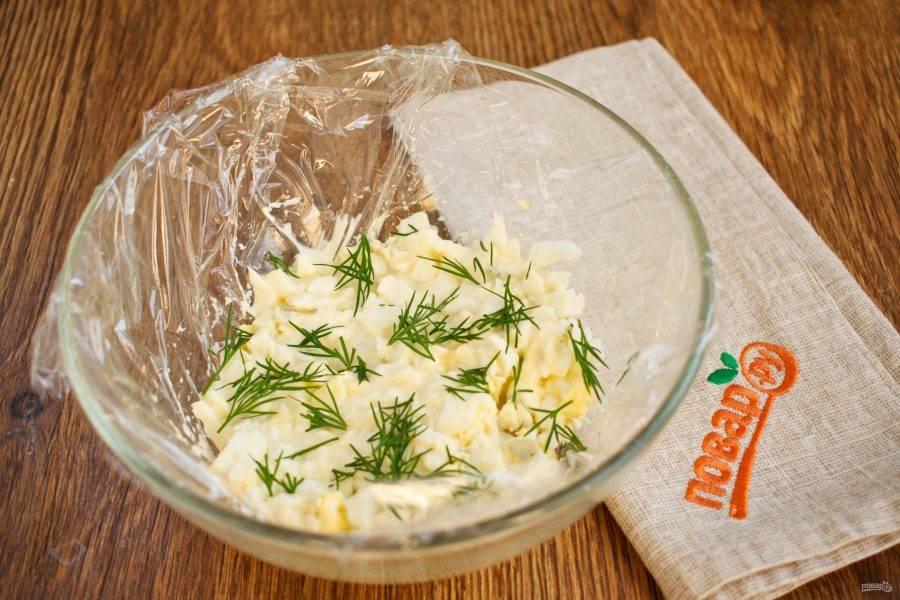 Круглую салатницу застелите пищевой пленкой. Выкладывайте салат слоями. Яйца, нарежьте кубиками, добавьте 1 ст. л. майонеза, перемешайте, посыпьте измельченным укропом.