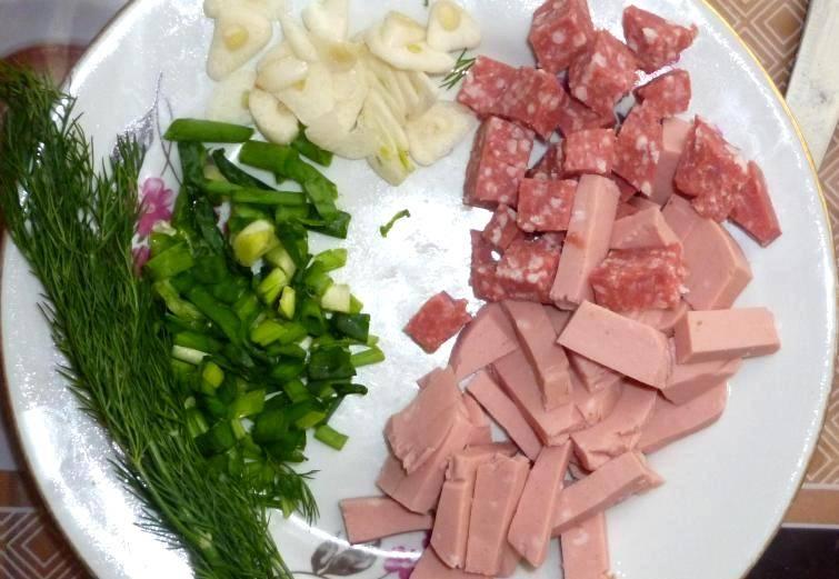 Нарезаем колбасу на небольшие кусочки, измельчаем свежую зелень, а чеснок нарезаем пластинками.