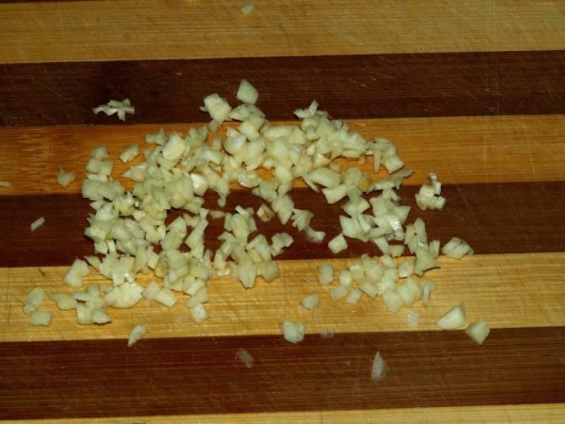 4. Измельчаем мелко чеснок и отправляем также к овощам.
